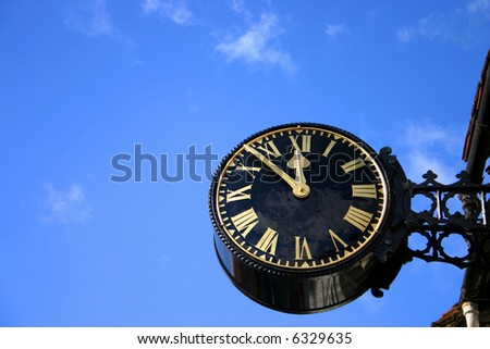 A large public clock photographed against blue sky - stock photo