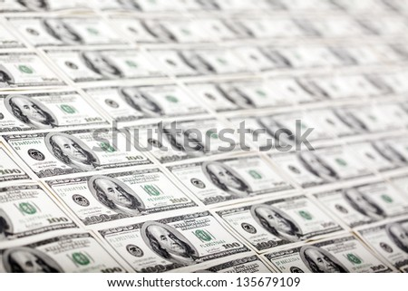 A large quantity of 100 US$ money notes lined up in a vertical row. Very shallow depth of field. - stock photo