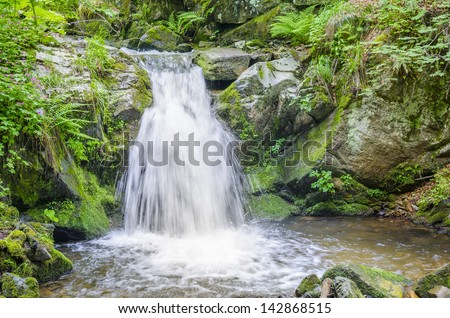 A large rain forest waterfall plunges off a cliff onto mossy rocks - stock photo