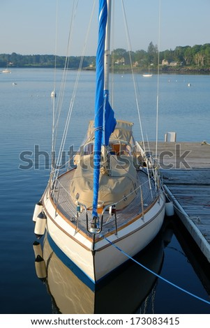 A large recreational sailboat docked in a calm protected harbor - stock photo