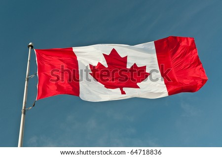 A large red and white Canadian flag ripples in a strong breeze.