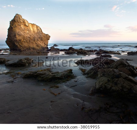 A large rock on a california beach is highlighted by the setting sun