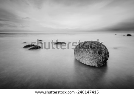A large rock on the beach being surrounded by the incoming tide.