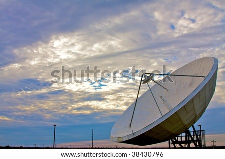 A large satellite dish points into a cloudy blue sky - stock photo