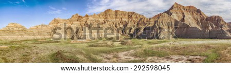 A large-scale panoramic view of a part of Badlands National Park in South Dakota showcases the grasslands and the hills of the area.