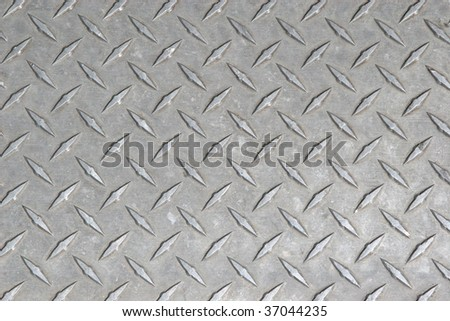 A large seamless sheet of slightly worn and scratched aluminum or nickel diamond or tread plate. - stock photo