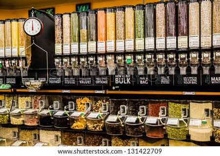 A large selection of bulk dry foods in clever dispensers and a weighing scale at an upscale grocery store - stock photo