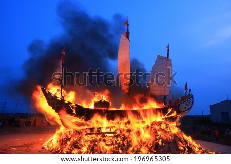 A large ship that has been set on fire. - stock photo