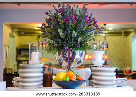 A large silver vase of flowers on a table with dishes and fruit in the lobby restaurant/A large silver vase of flowers on a table with dishes and fruit in the lobby restaurant. - stock photo