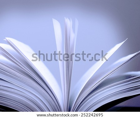 A large single book sitting with pages open on a desk - stock photo