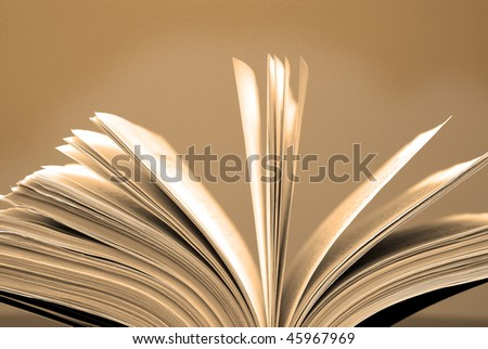 A large single book sitting with pages open on a desk and brown background - stock photo