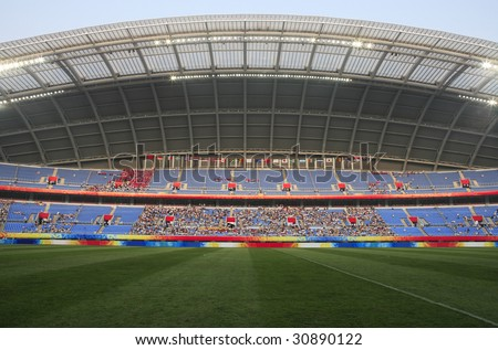 A large sports stadium filling with fans before the start of a soccer match. - stock photo