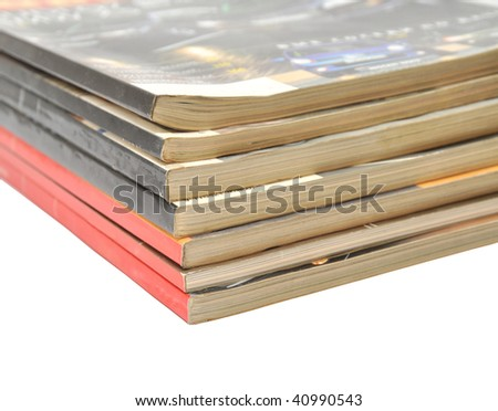A large stack of magazines piled high isolated on white backgound - stock photo