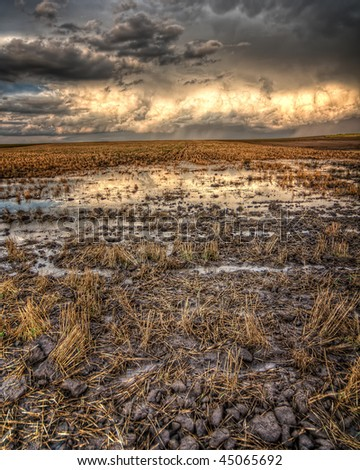 A large storm leaves a flooded field in its wake - stock photo