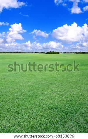 A large stretch of open, grass-covered land, closely mowed. - stock photo
