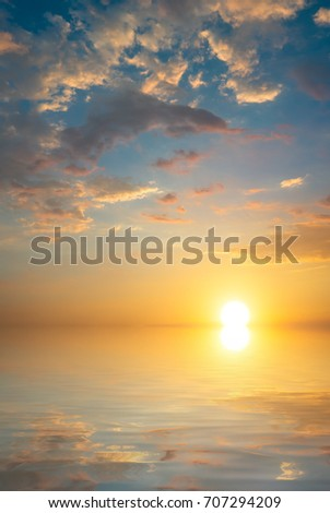 A large sun rises over the sea against a background of sunset clouds. Sunset composition