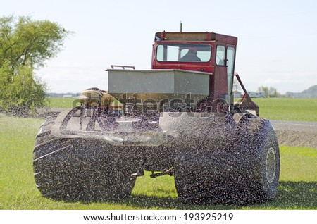A large swamp buggy type tractor distributes fertilizer to a field or pasture of grass in the Willamette Valley of Oregon - stock photo