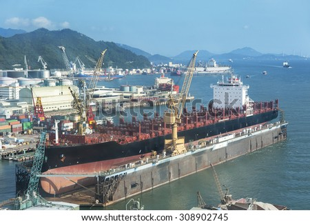 A large tanker ship is being renovated in shipyard - stock photo