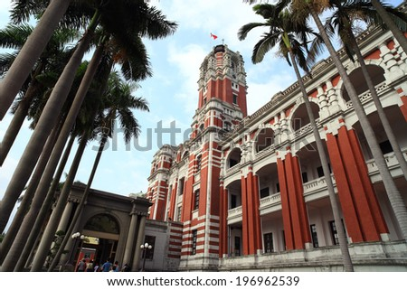 A large three level building with palm trees in the foreground. - stock photo