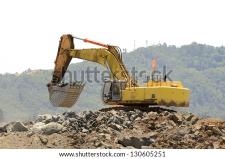 A large track hoe or tracked excavator  moving rock from a hill at an airport runway expansion project