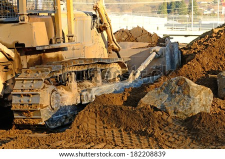 A large tracked bulldozer on a hill pushing soil and rock on a new commercial road construction project