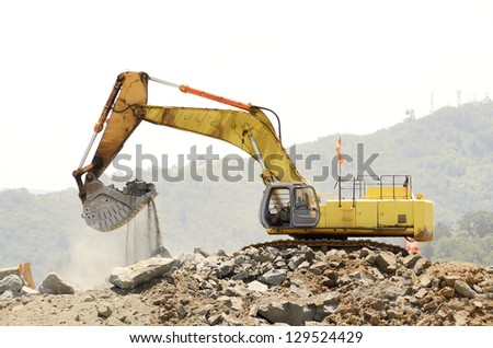 A large trackhoe or tracked excavator  moving rock from a hill at an airport runway expansion project
