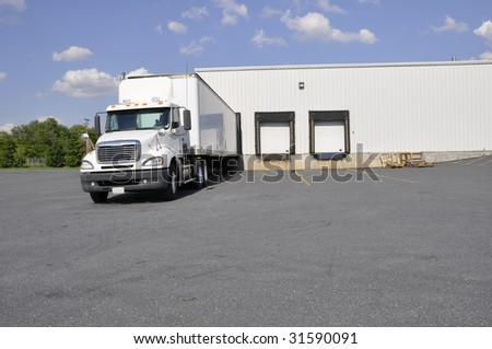 a large truck at an unloading dock for a warehouse - stock photo