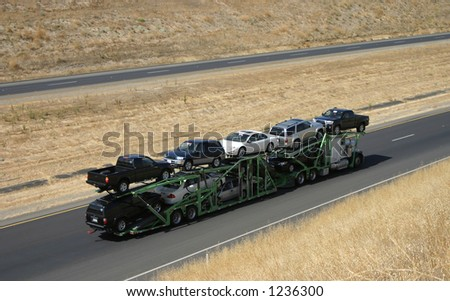 A large truck delivers new cars via highway. - stock photo
