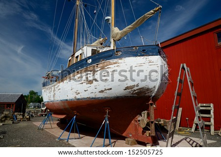 A large twin masted sail boat and trawler in a boatyard being repaired and restored - stock photo