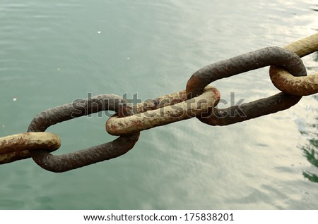 A large vintage anchor chain spans the water