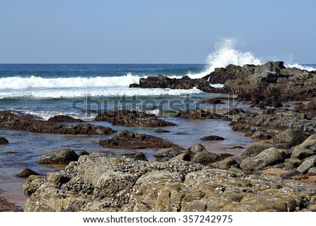 A large waves crashes into a rock on a beach, sending water spraying into the air. - stock photo