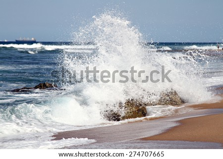 A large waves crashes into a rock on a sandy beach, sending water spraying into the air. - stock photo