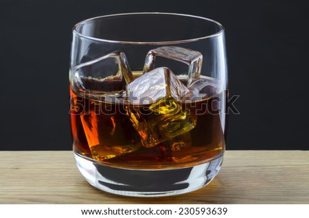 A large whiskey poured over ice cubes in a plain glass - stock photo
