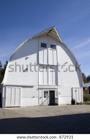 A large white barn with a blue sky background