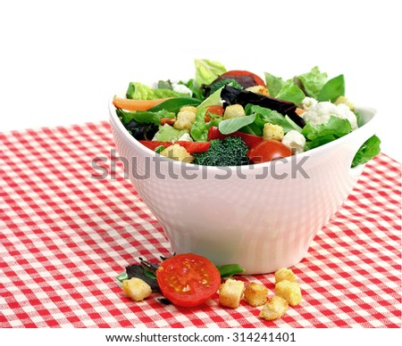 A large white bowl of mixed vegetable salad with greens, tomatoes, broccoli,cauliflower, feta and bread cubes.