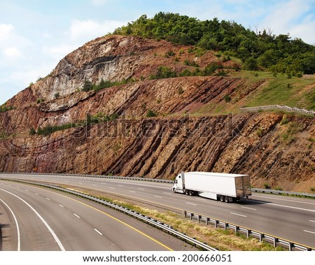 A large white trailer truck drives through a mountain pass with steep sedimentary rock to the sides of the road. - stock photo