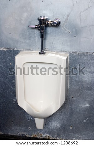 A large white urinal in the mens restroom - stock photo