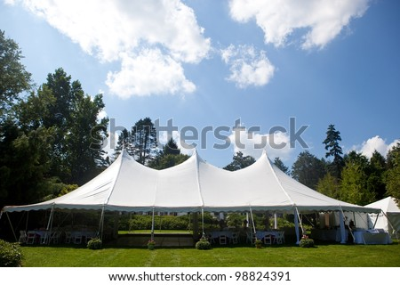 A large white wedding tent set up for an outdoor function or banquet
