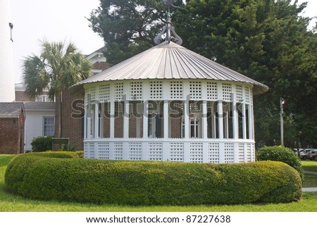 A large white wooden gazebo in a green landscaped garden - stock photo