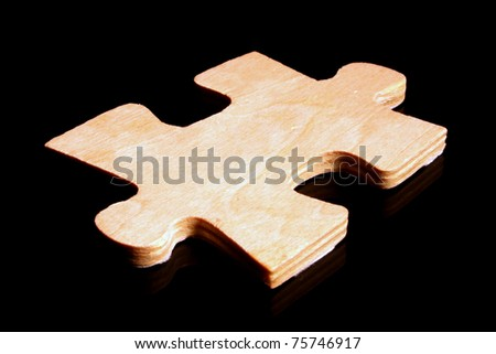 A large wooden puzzle piece on a black surface - stock photo