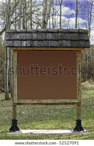A large wooden sign in the forest, left blank for your text