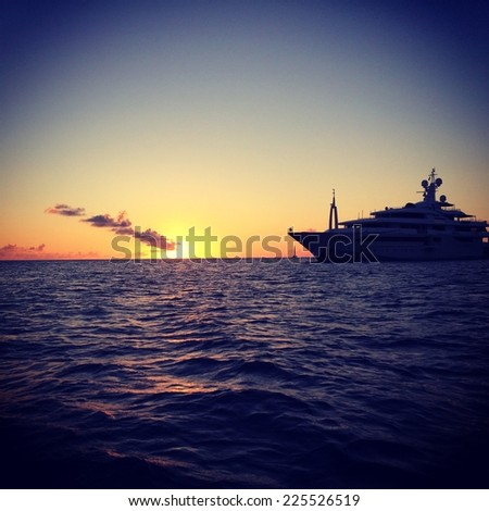 A large yacht in a calm blue sea under a setting sun. - stock photo