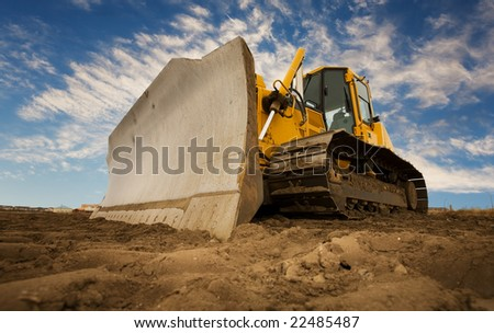 A large yellow bulldozer at a construction site low angle view - stock photo