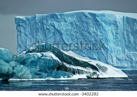 A larger blue iceberg in the background is partly hidden by a smaller so-called black iceberg in the foreground, the latter partly being covered by snow.
