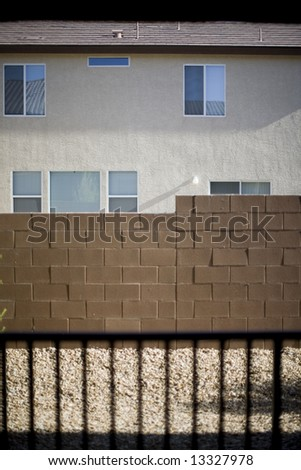 a las vegas stucco house sits behind a brick wall and a shadow of a fence with each distinct object making a different pattern outside - stock photo