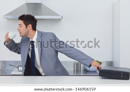 A late businessman taking his briefcase and drinking a coffee while going to work - stock photo