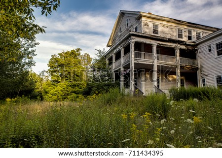 A late evening view of an abandoned resort surrounded by wildflowers and tall grasses in the Catskill Mountains of New York.