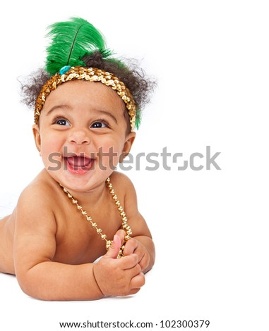 A laughing baby wearing a gold sequin flapper headband with a tall green feather in it and a gold necklace. Isolated on white with extra room for your text - stock photo