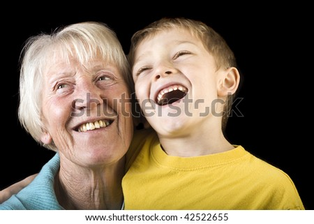 a laughing blonde child and his grandmother