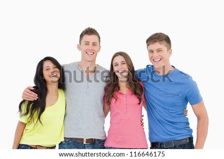 A laughing bunch of friends standing and holding each other as they all look into the camera - stock photo